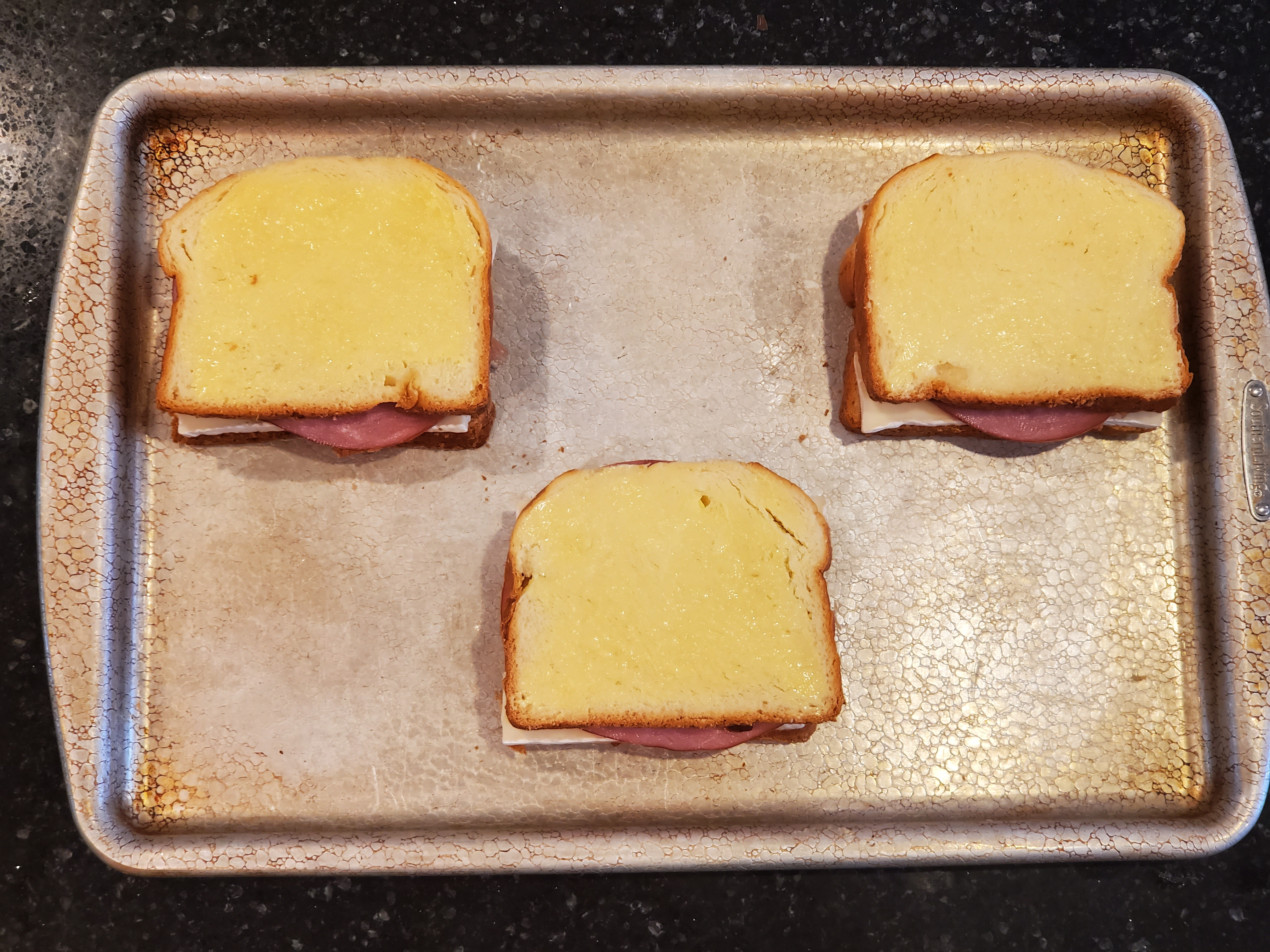 The three sandwiches are now assembled on top of the baking sheet, butter side up, ready to go in the oven.