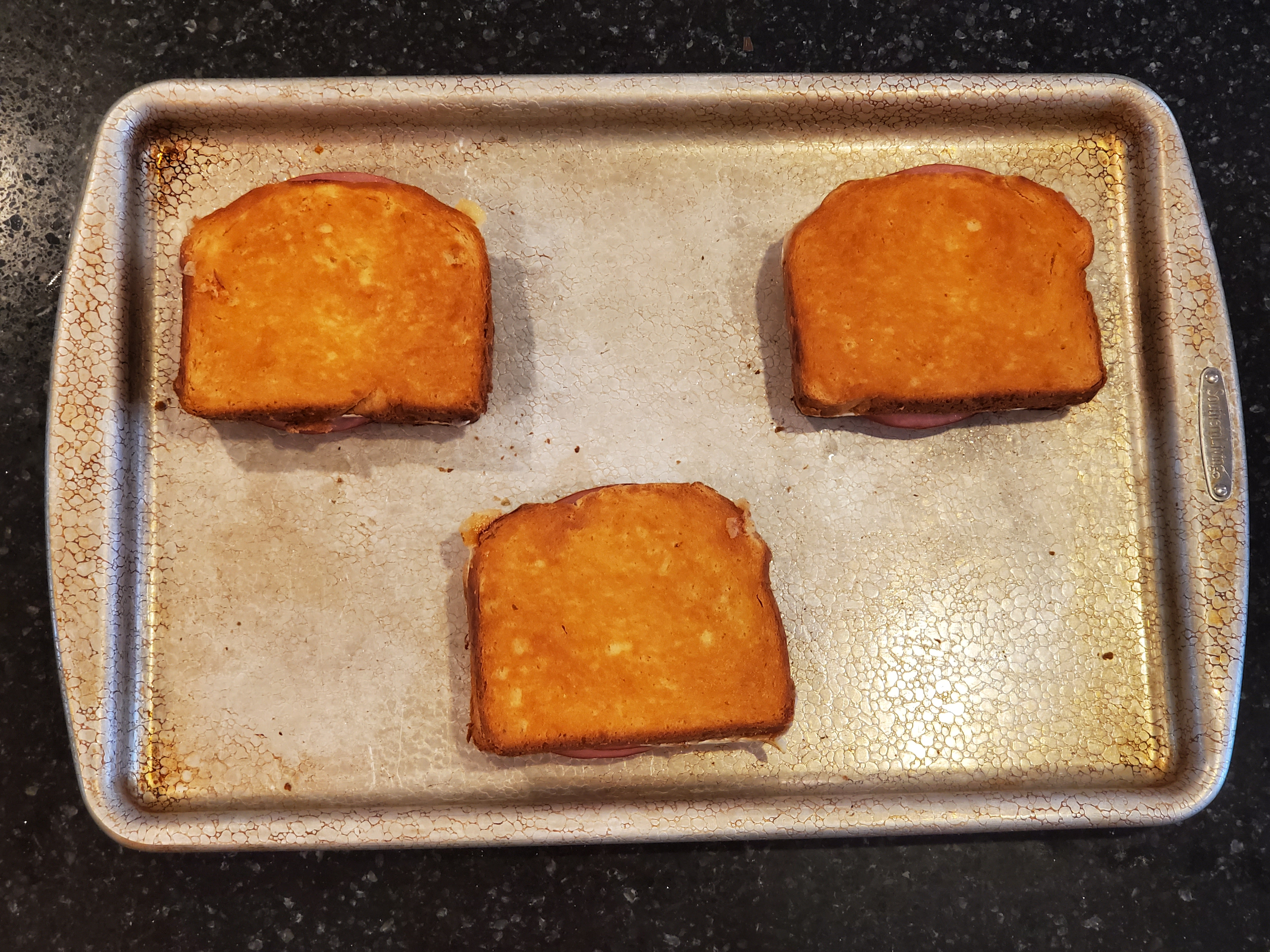 The three sandwiches have come out of the oven, golden brown and sit on the baking sheet.