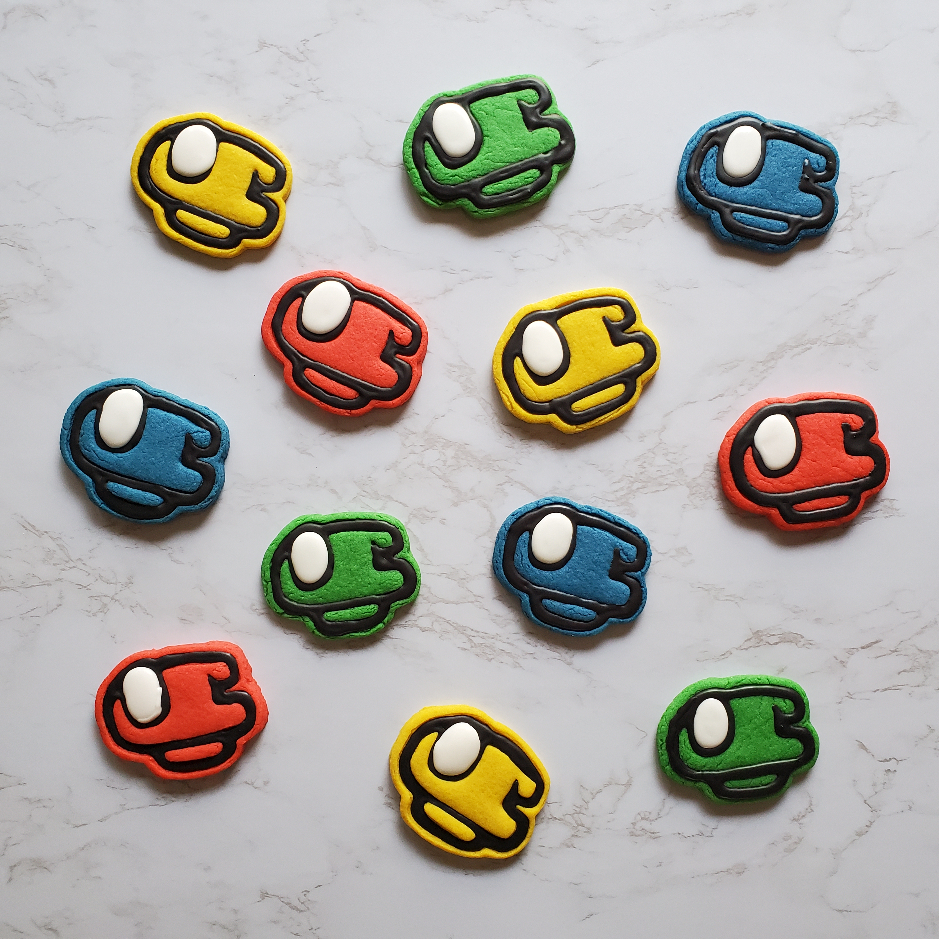 Among us cookies in the colors red, yellow, green and blue, laying on a marble countertop.