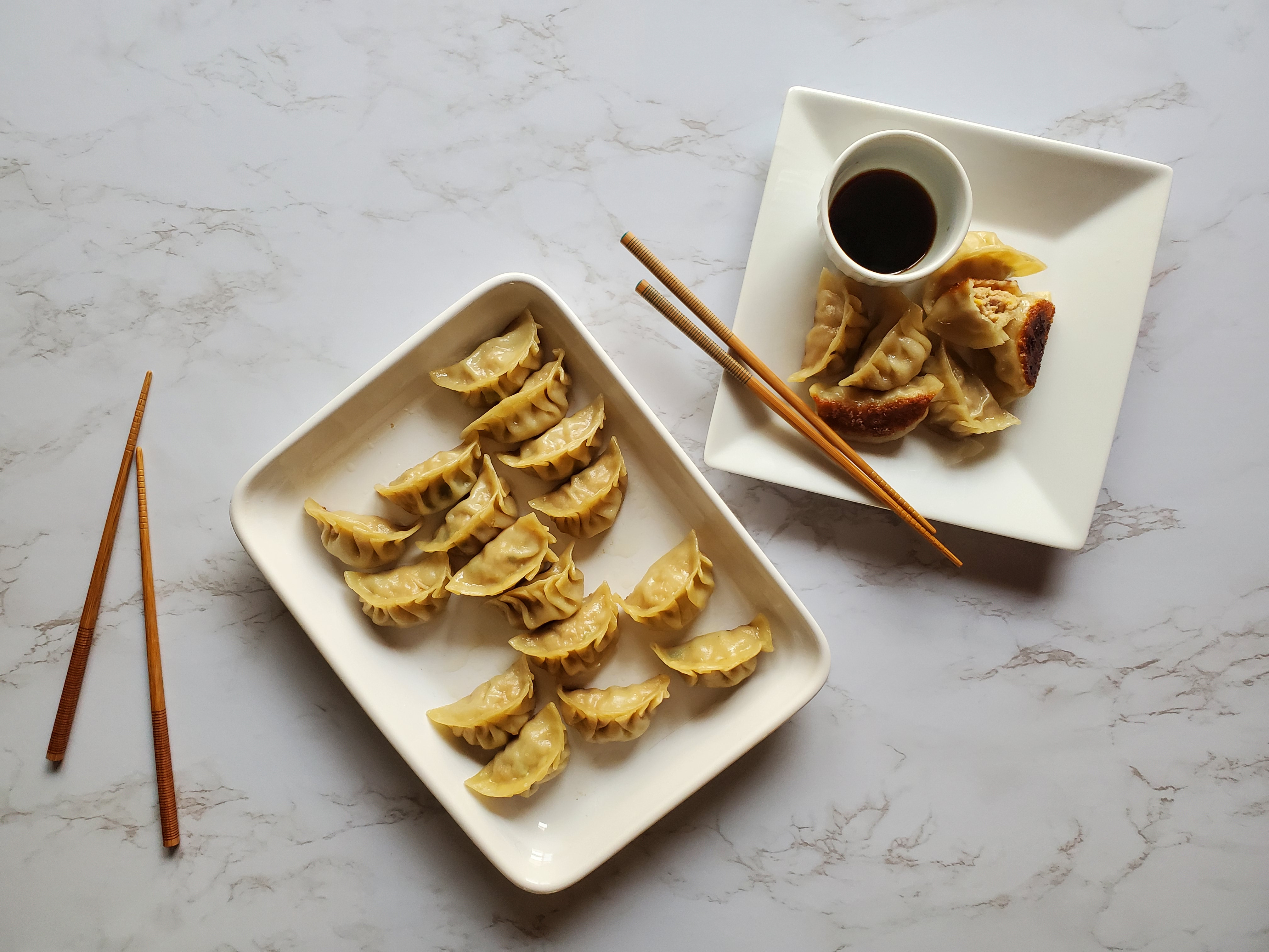 A large rectangular plater of Chinese Potstickers sits next to a square plate of potstickers with a small bowl of dark brown dumpling sauce. A pair of chopsticks rest on the square plate and on the left of the platter on the white marble coutertop.