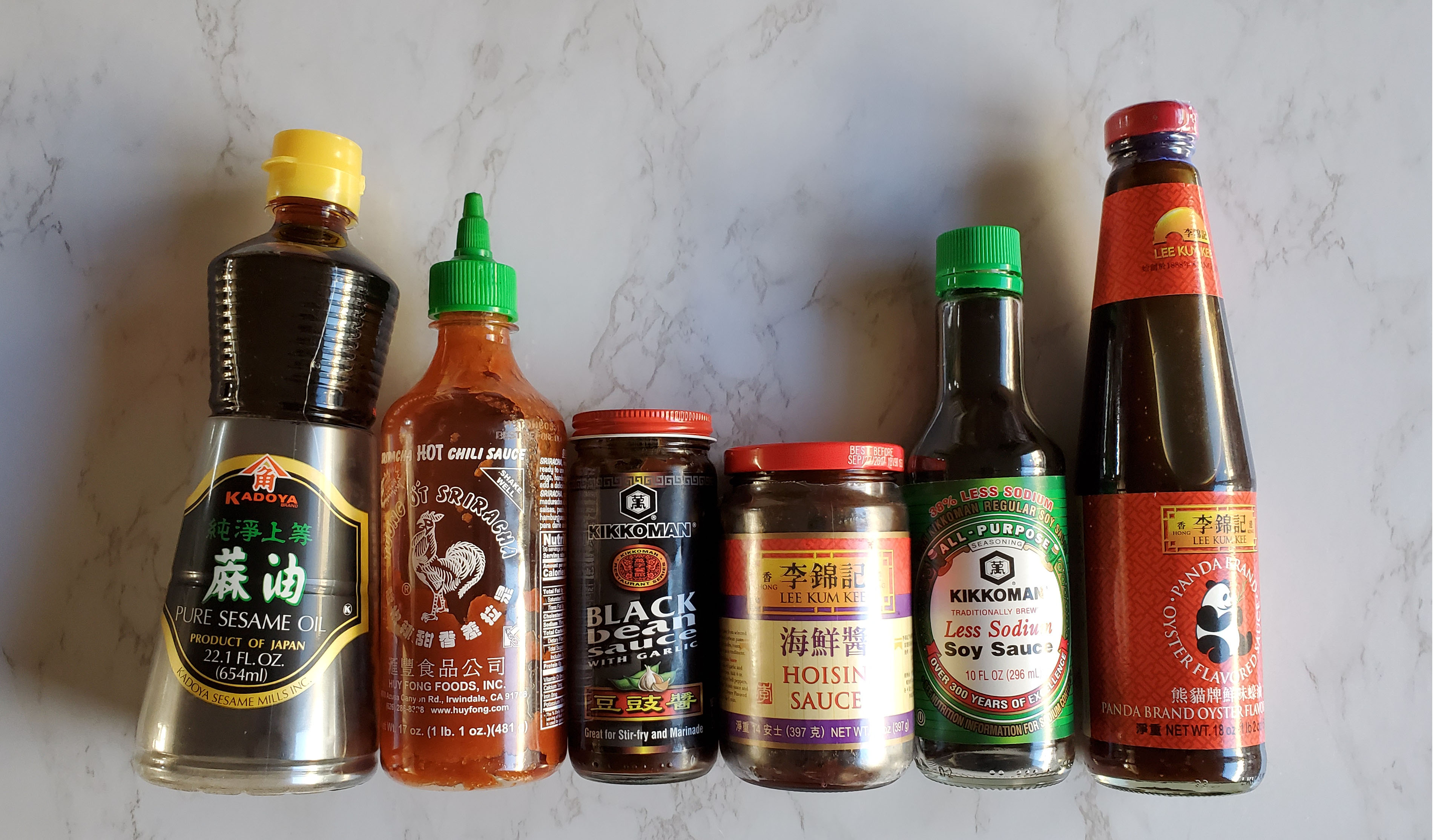From left to right a bottle of Kadoya Sesame oil, Sriracha, Black bean sauce, hoisin sauce, Kikkoman less sodium soy sauce and oyster sauce all against a white marble background.