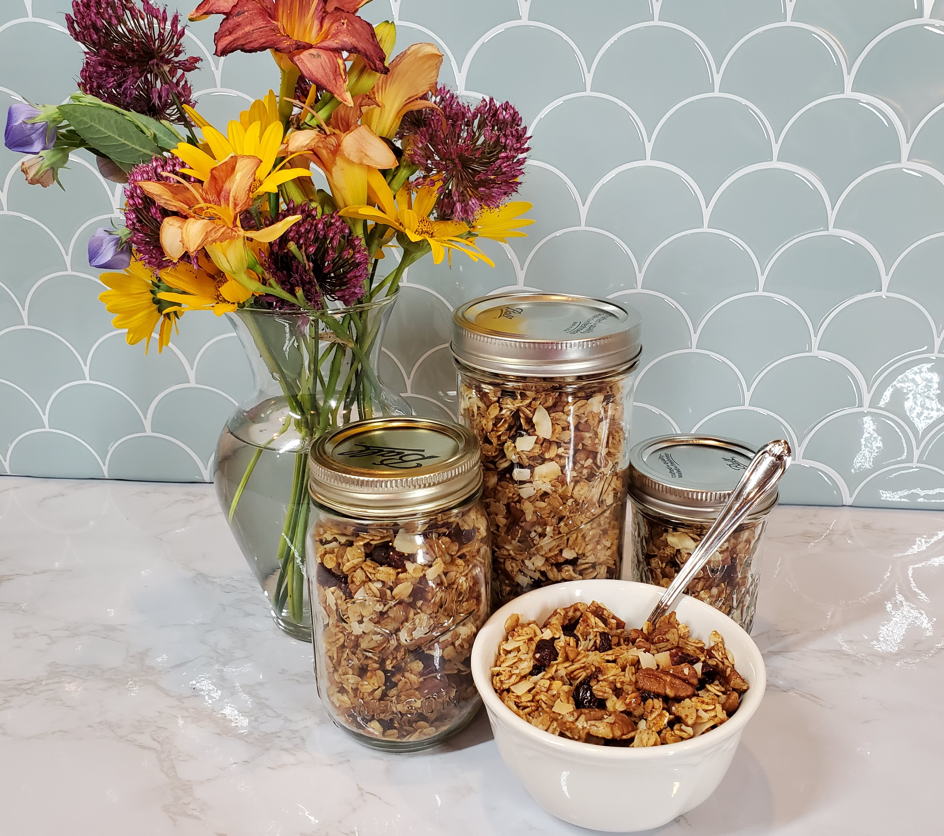 A bowl of pecan/craisin granola in a white bowl with a spoon sits in front of three Mason jars of granola on a white granite counter top. Behind it is a vase filled with yellow, pink and purple flowers and a shell turquoise tile backsplash.