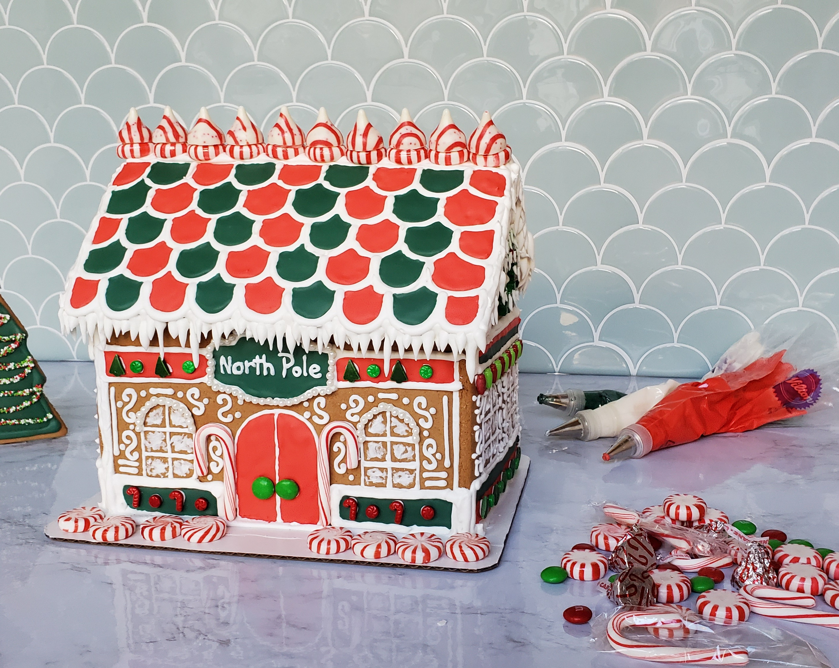 A gingerbread house surrounded by peppermints, candy canes, and royal icing.