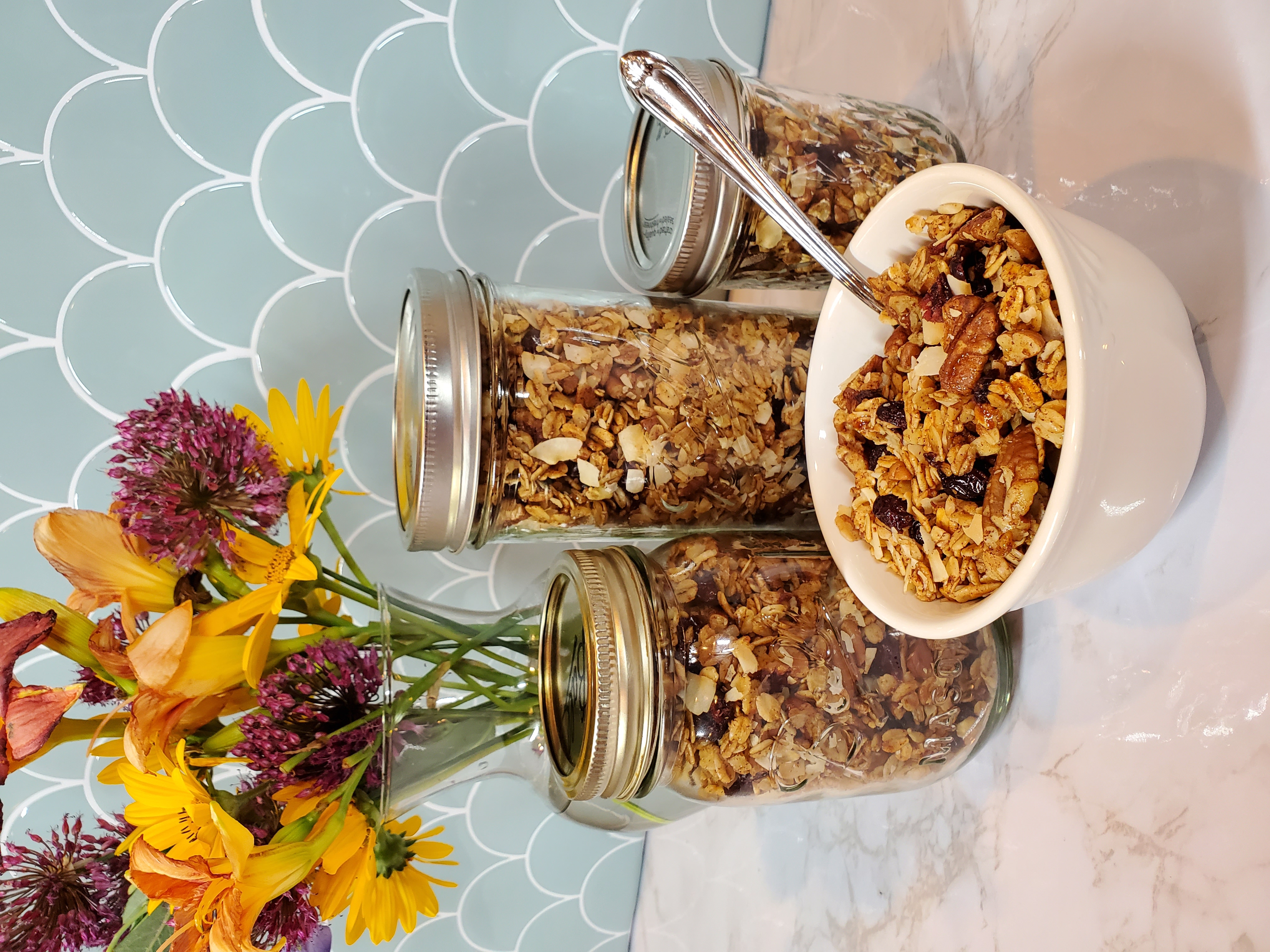 Three jars of granola sit behind a bowl of granola. Bits of pecans and craisins are visible. There is a siler spoon sticking out of the bowl and there is a vase full of flowers behind the scene, yellow, pink and purple.