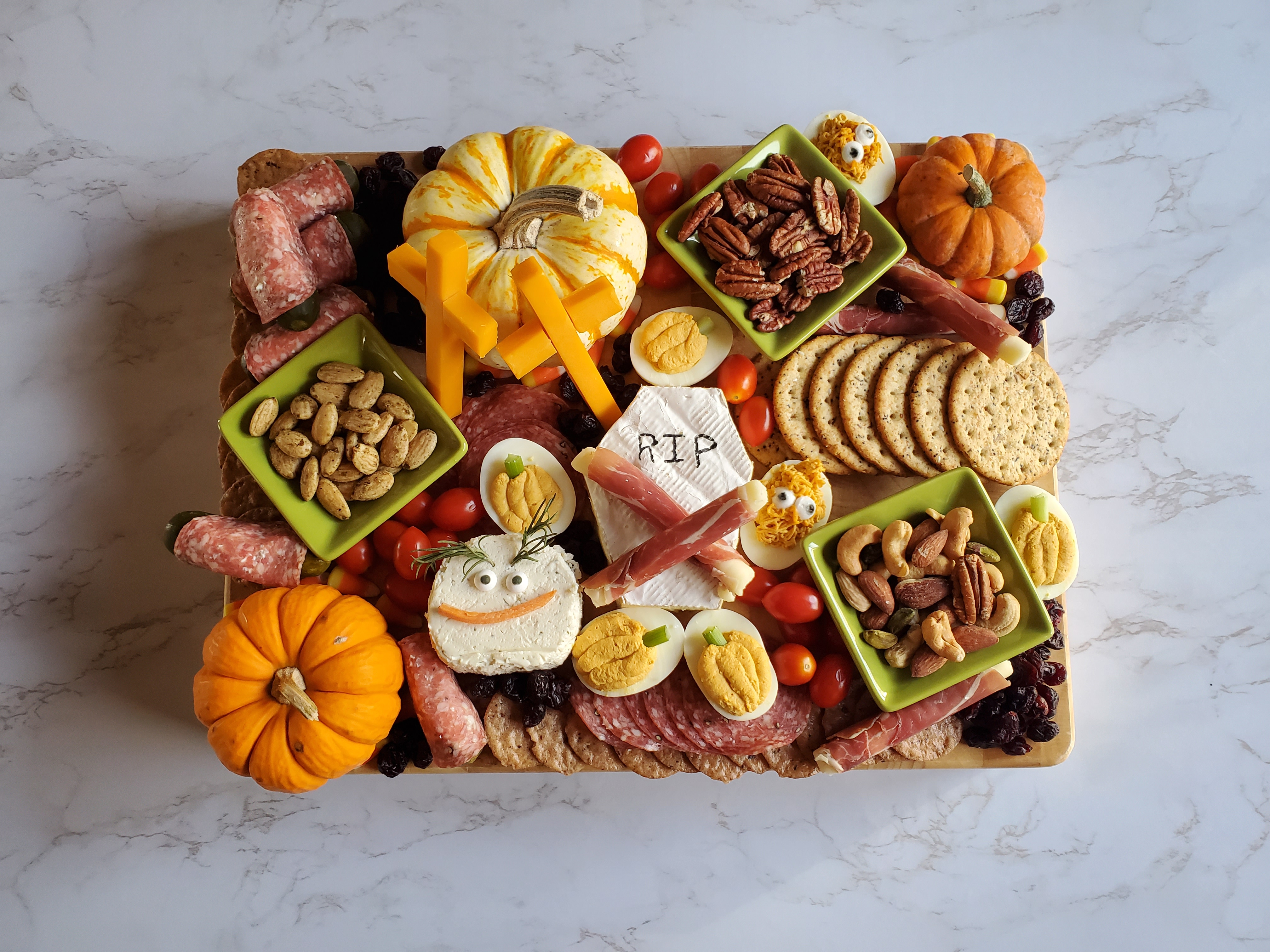 A large charcuterie board filled with a brie tombstone, mini pumpkins, cheese stick crosses, pumpkin deviled eggs, nut, dried meats and grape tomatoes on a marble countertop.