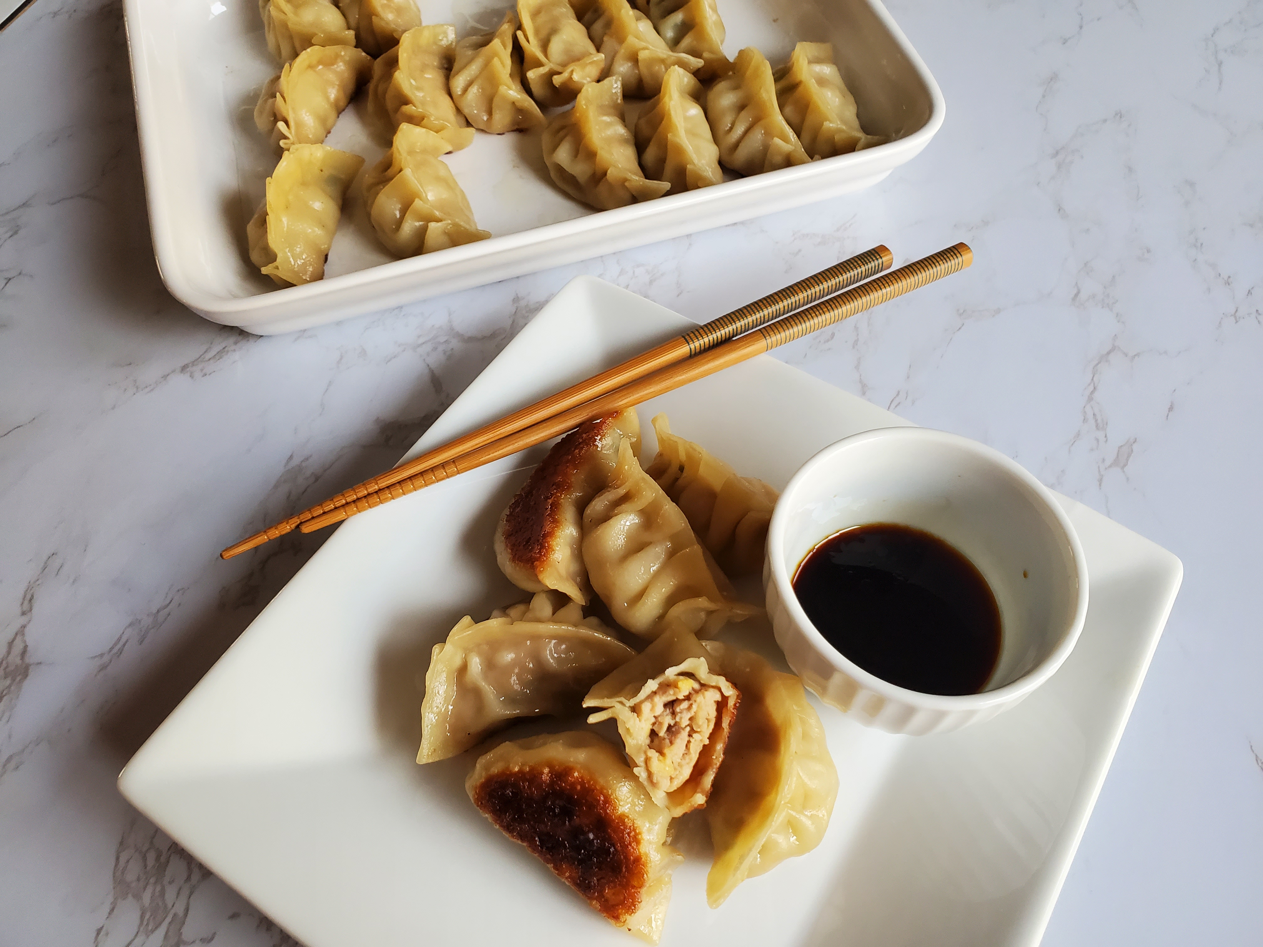 In the background, a picked over platter of potstickers. In the foreground is a square plate with a round cup of dark brown dumpling sauce surrounded by potstickers, one has a bite taken out. A pair of chopsticks rests on the upper left.