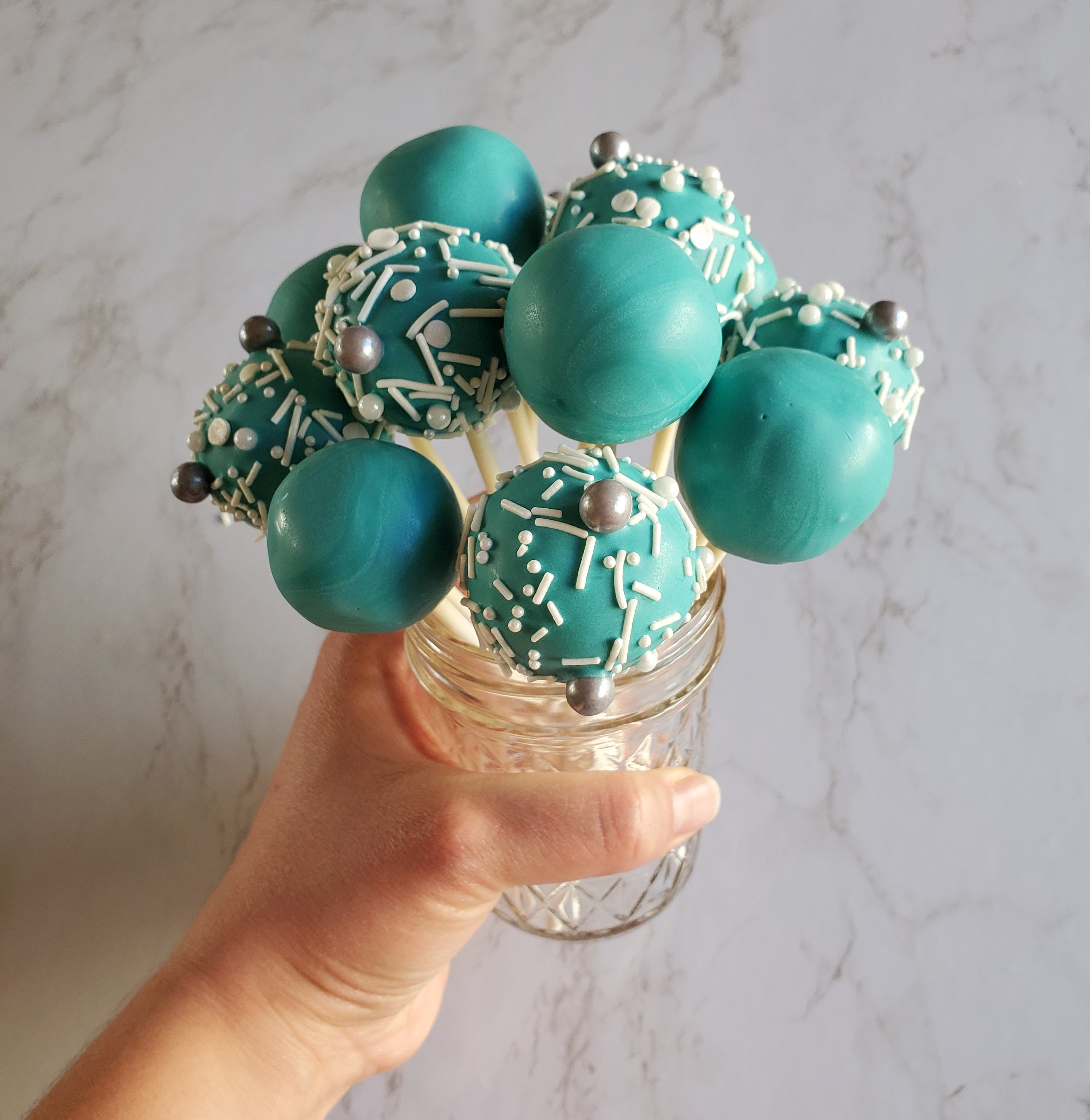 A bouquet of turquoise sprinkled cake pops in a glass jar, held up by a hand in front of a marble background.