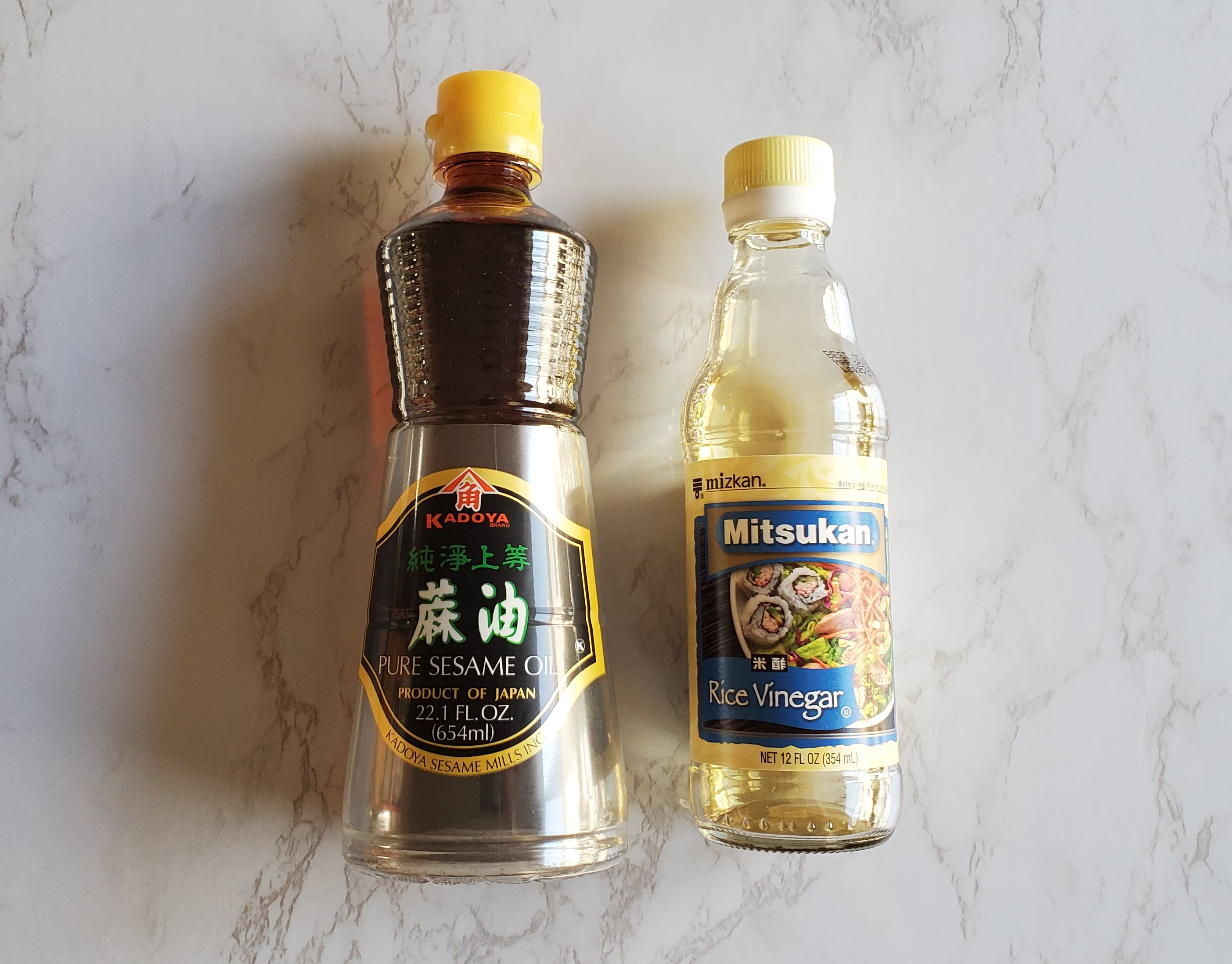Sesame oil and rice vinegar on a white marble background.
