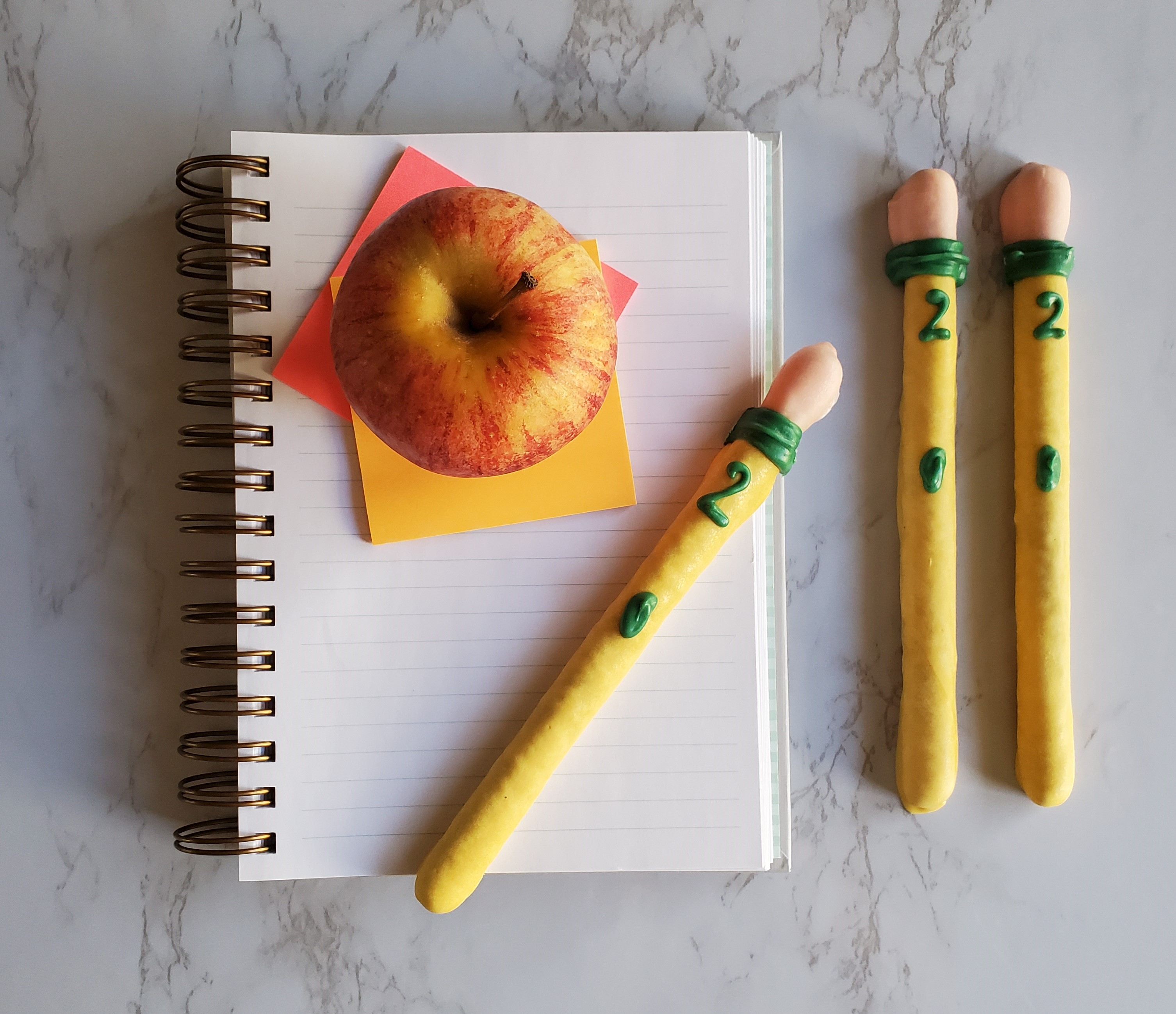 "Candy ""pencils"" made from pretzel rods lay on top of a school ruled notebook and post-its with a lunch room style apple on top of a marble counter."