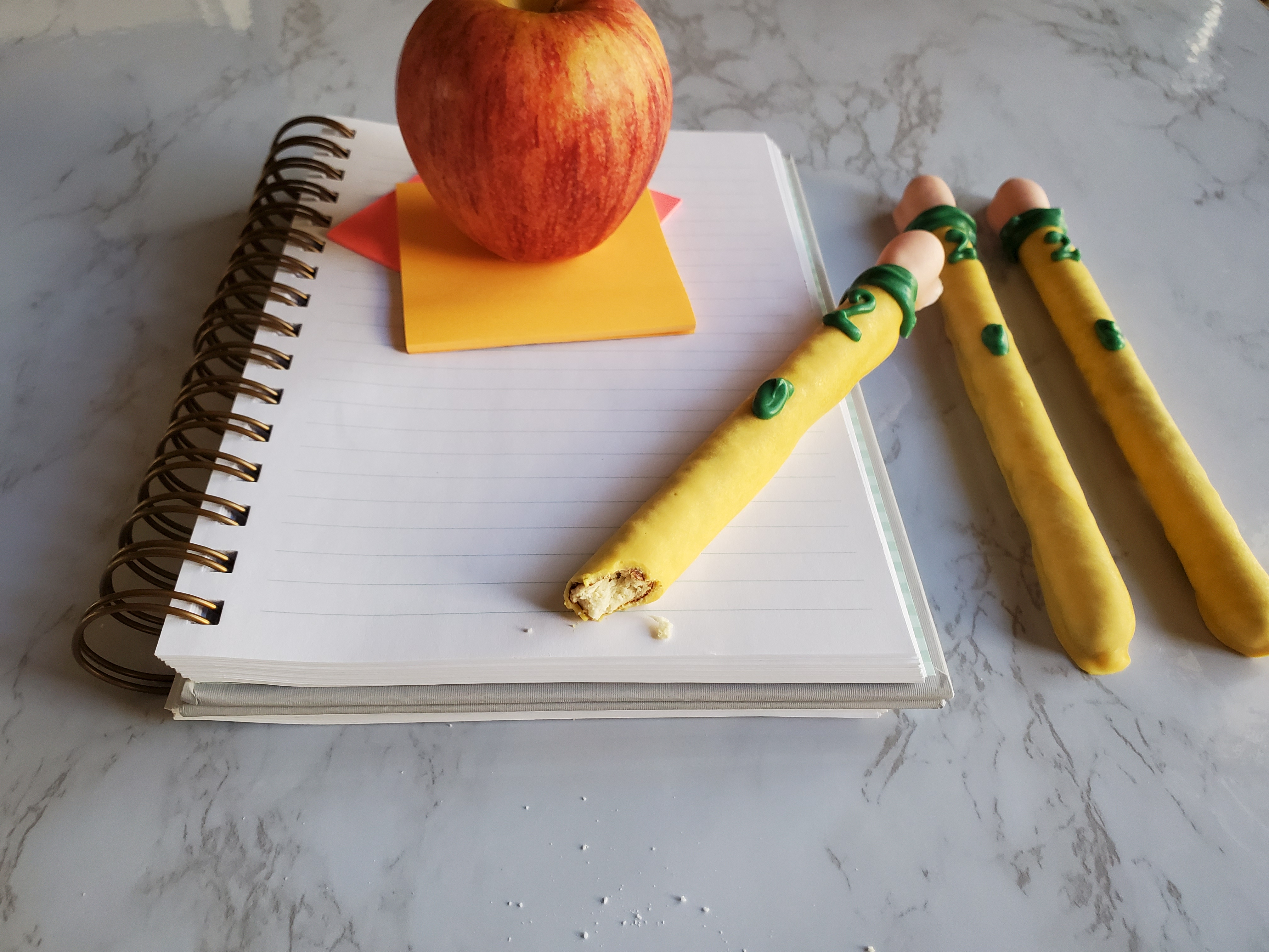 A notebook with bright pink and orange post-it notes, topped with a school lunch apple. A chocolate covered pencil pretzel sits on top of the notebook with a bite out of it, with two others to the right.