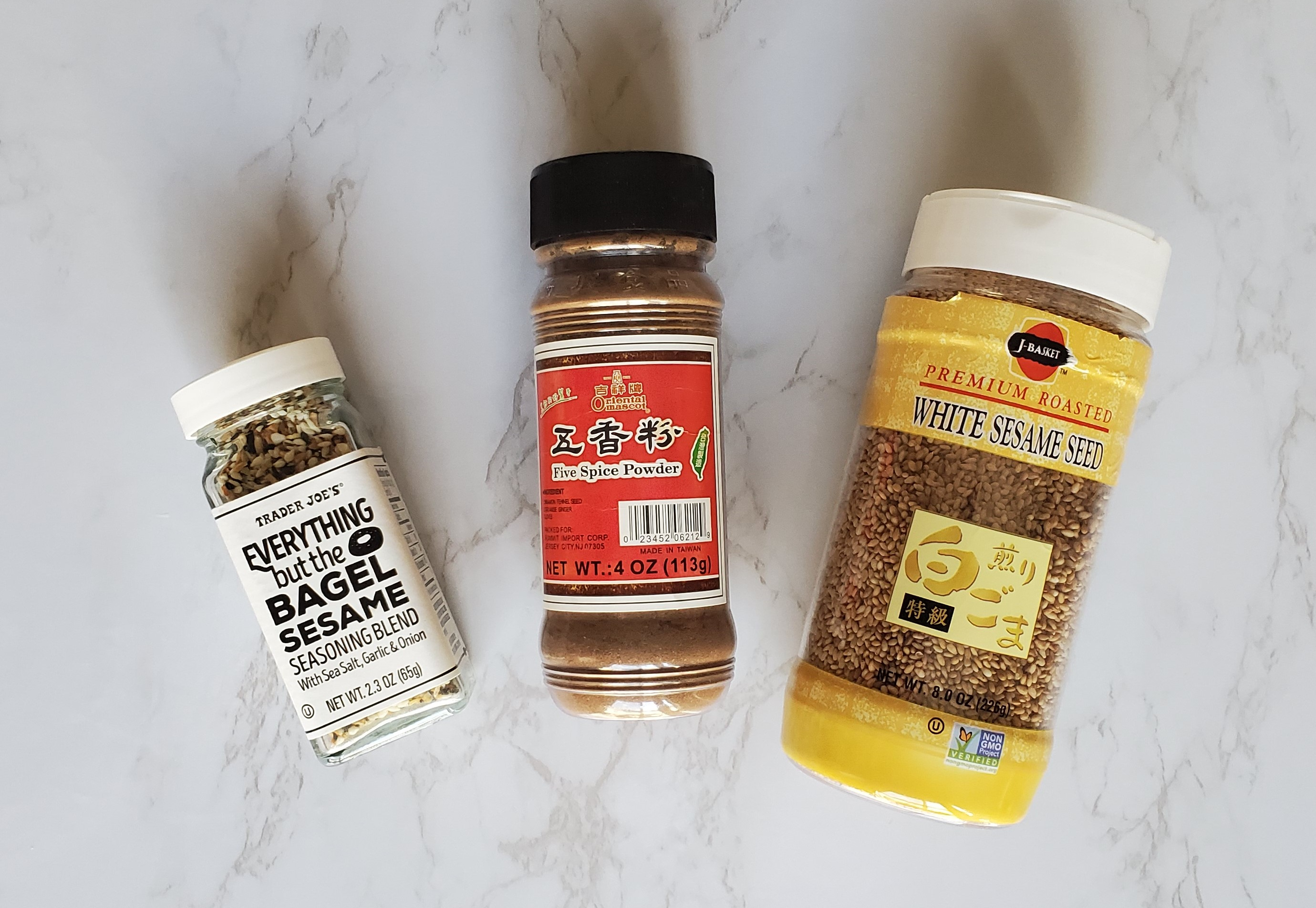 From left to right, a small jar of Trader Joe's Everything But the Bagel Seasoning, a jar or Chinese Five Spice and a large jar of white sesame seeds.
