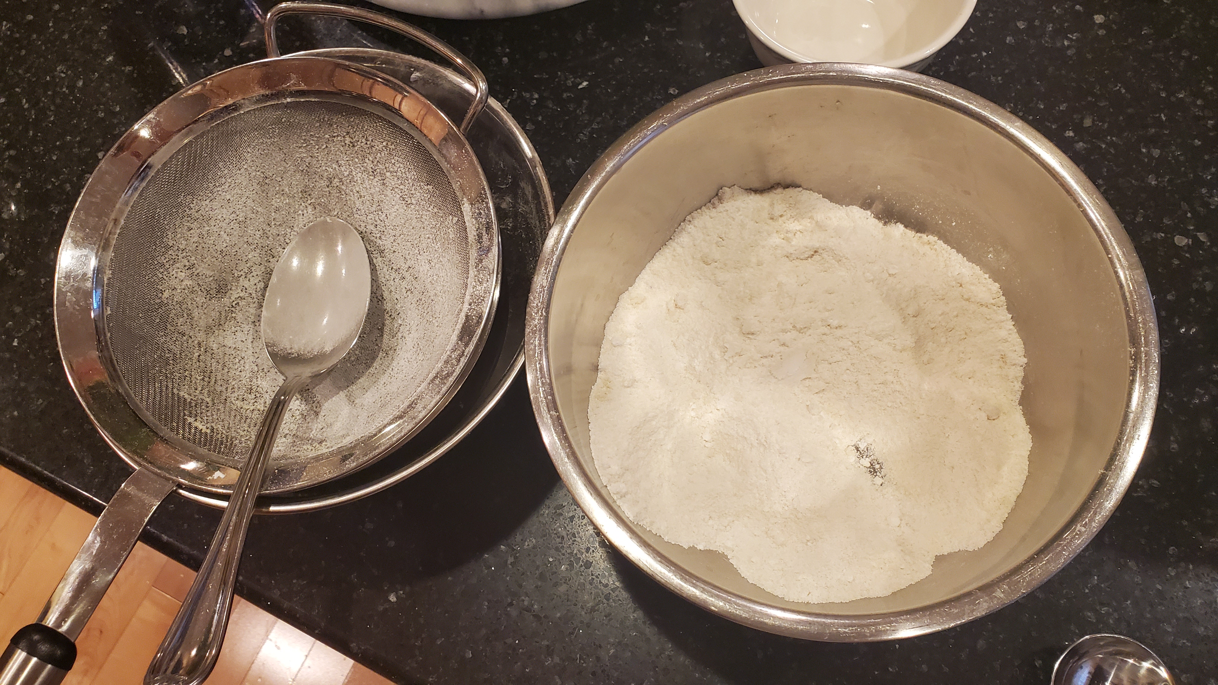 Powdered sugar and almond flour being sifted from a mesh strainer to a medium stainless steel bowl.