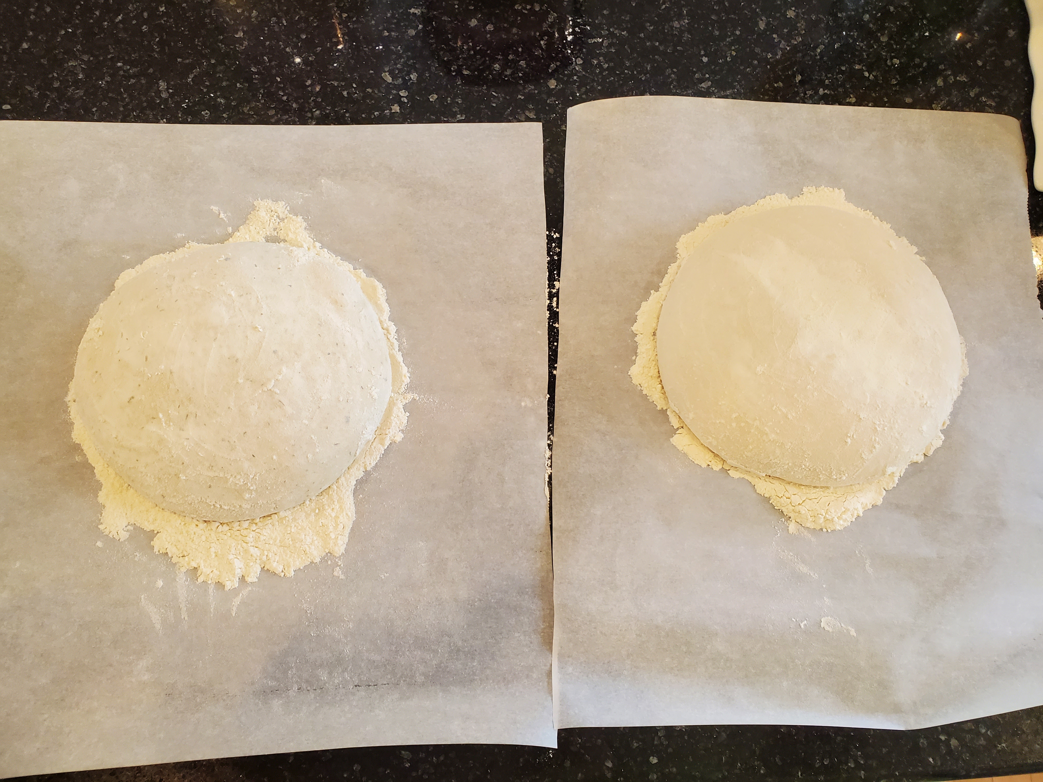 Two balls of sourdough rising on floured parchment paper on a black granite coutertop.