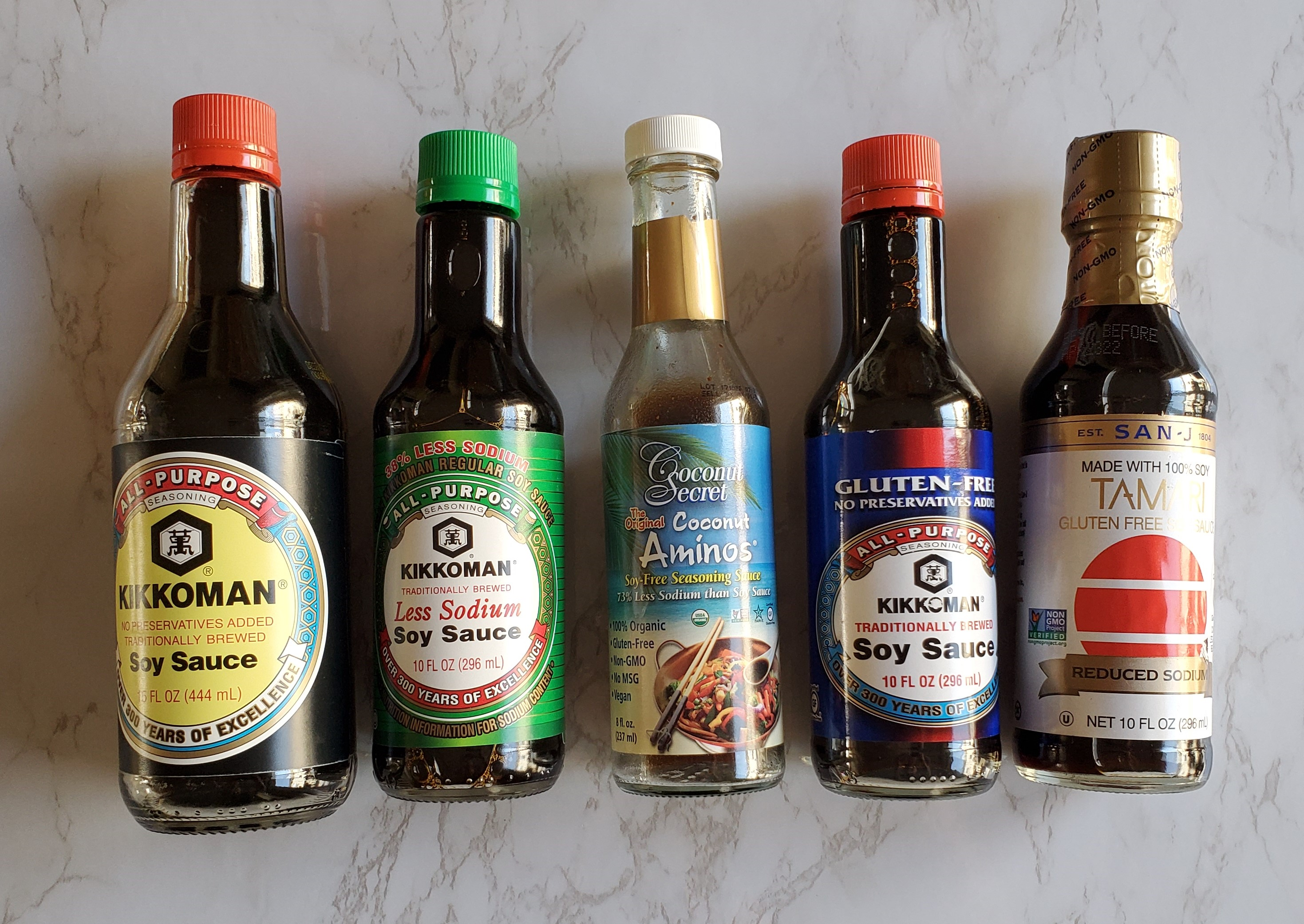 From left to right, Kikkoman Original Soy sauce, less sodium soy sauce, coconut aminos, GF soy sauce and Tamari.