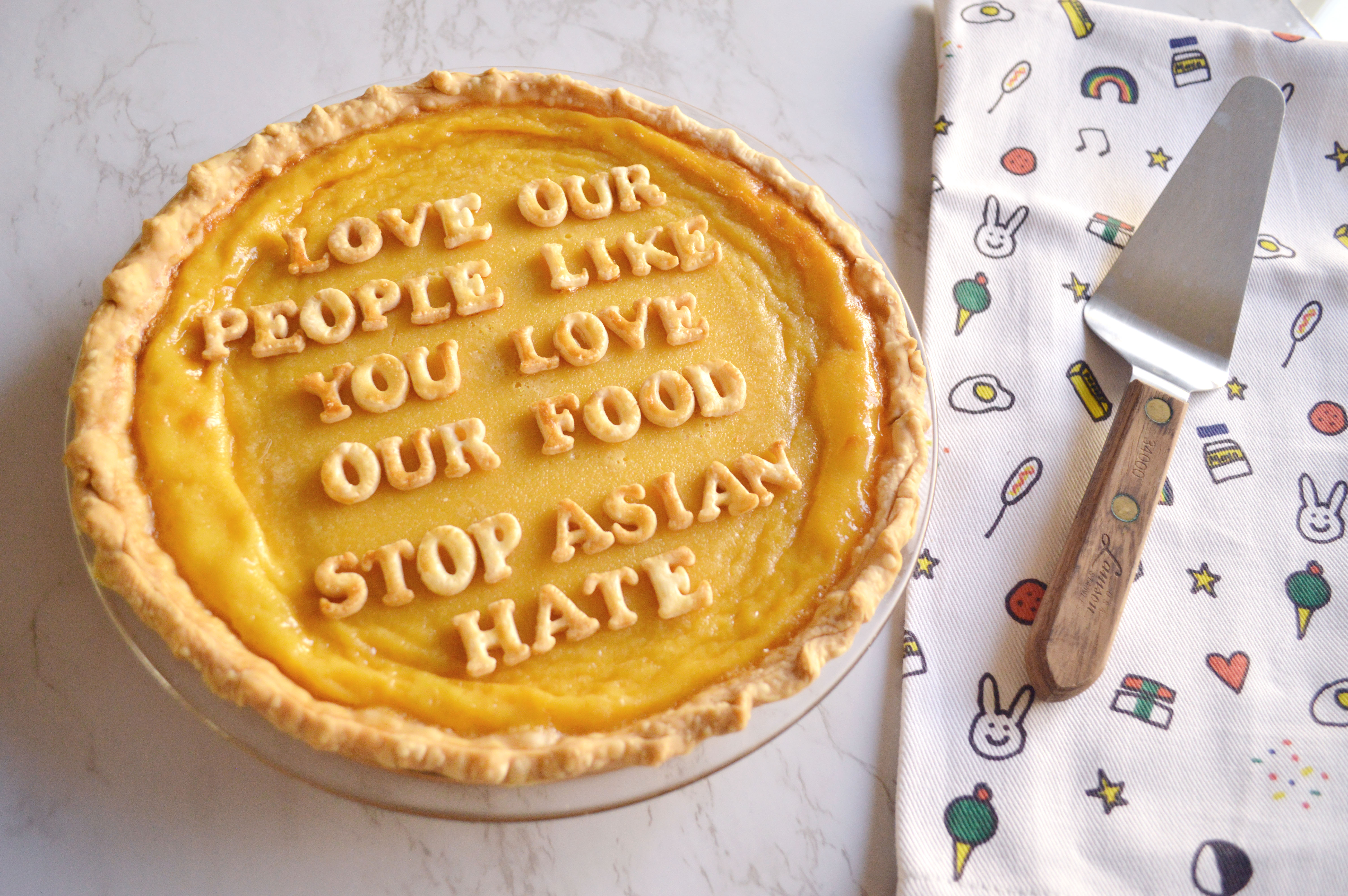 "A giant egg tart sits in the lower left corner with pie crust letters spelling out ""Love Our People Like You Love Our Food"". It sits on a Molly Yeh No Kid Hungry dish towel with a pie turner on it's righthand side."