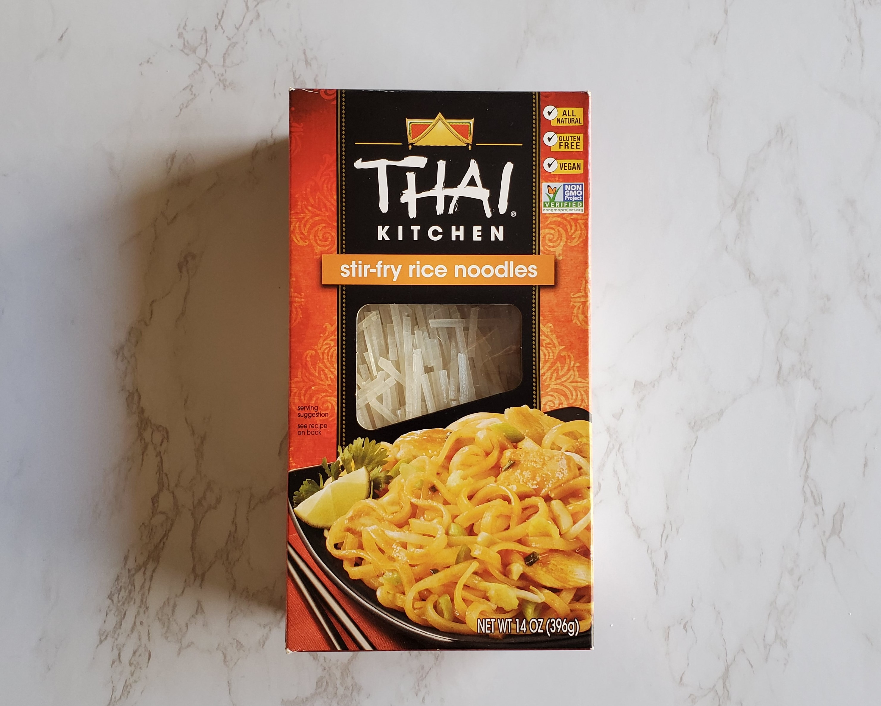 A box of Thai Kitchen stir-fry rice noodles on a white marble background.