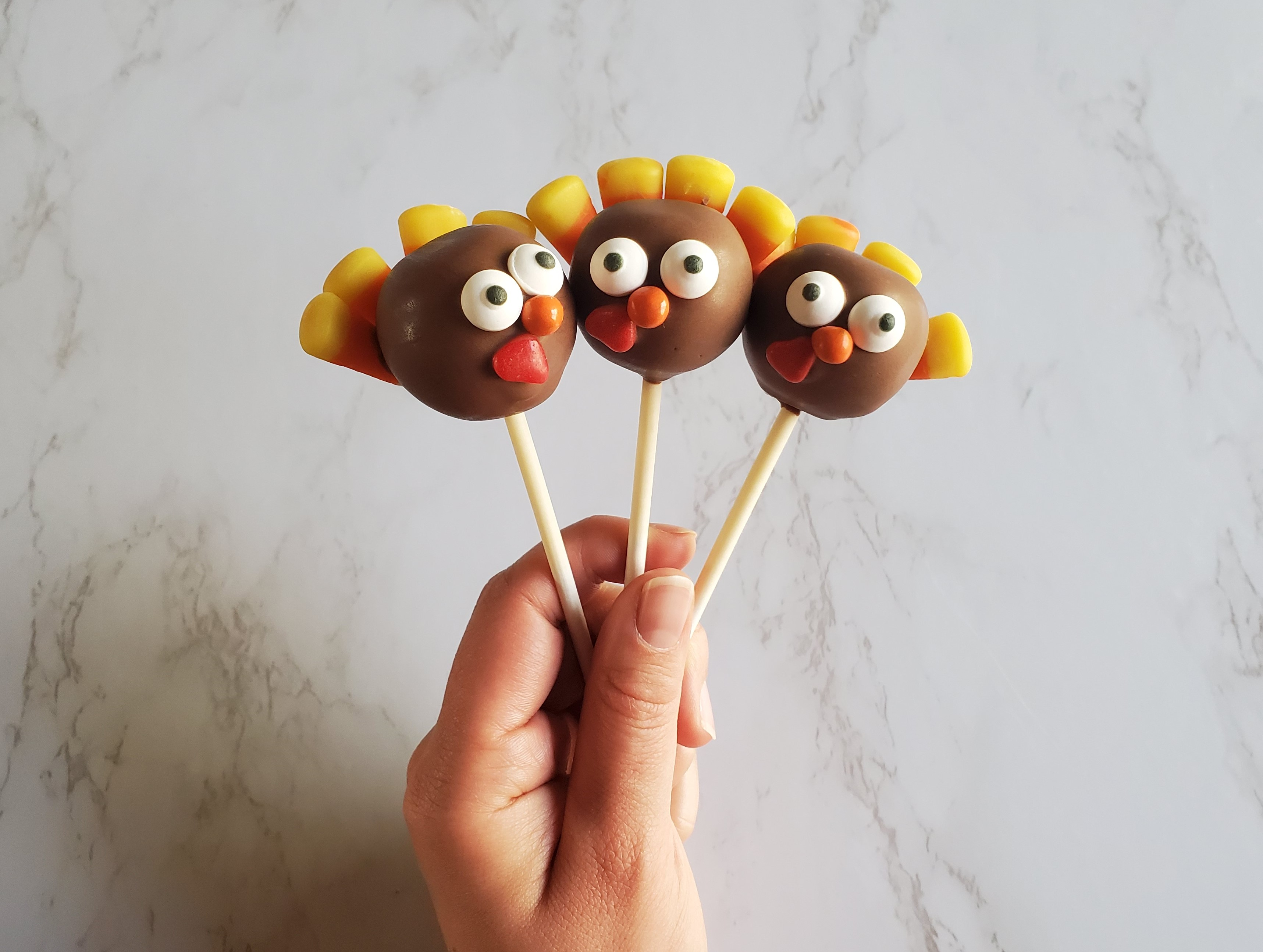 A hand holds up three cake pops decorated with candies including candy corn feathers to looks like turkeys in front of a marble background.