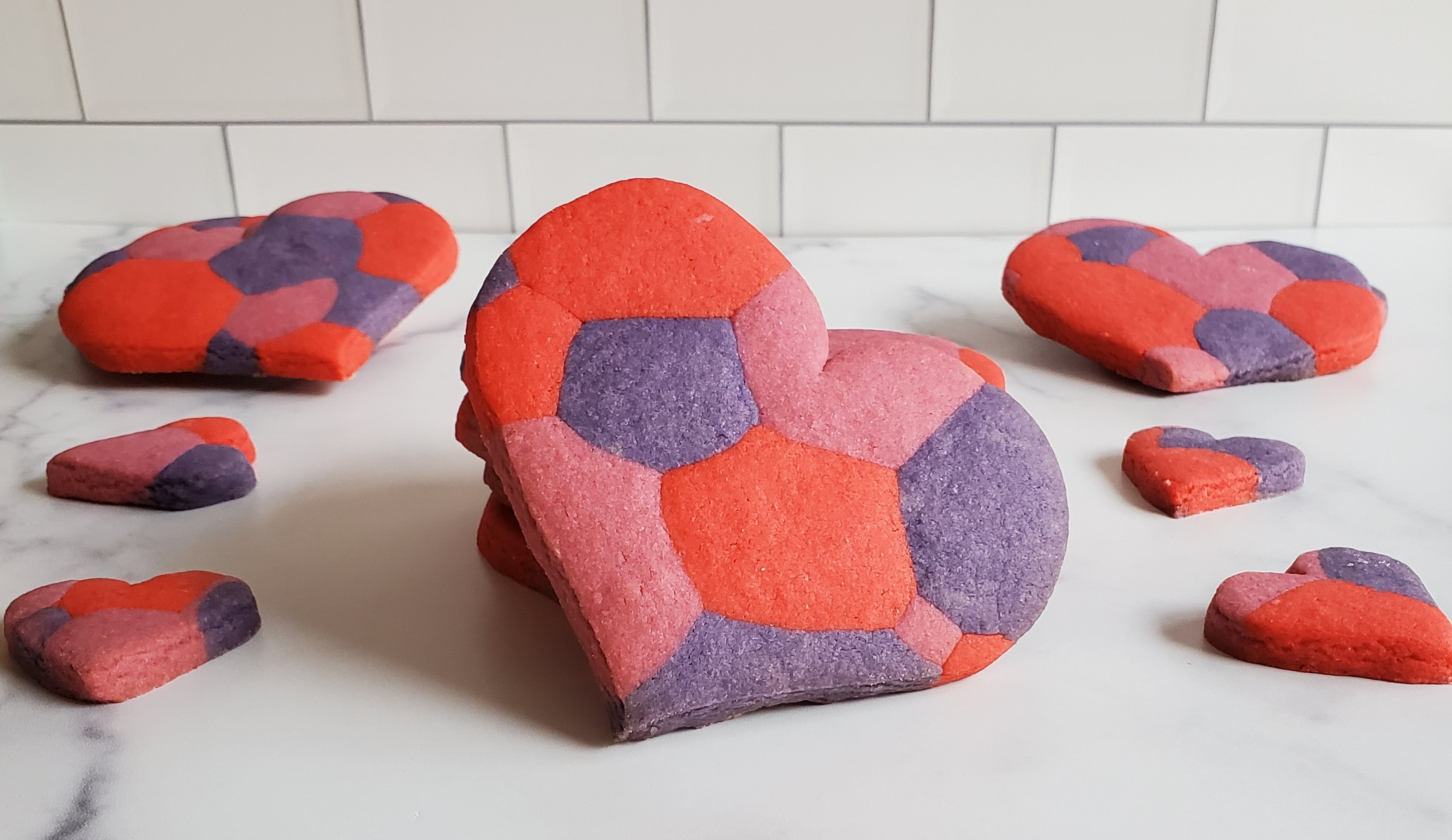 A large heart shaped sugar cookie with a marbled/mosaic pattern sits resting against a stack of more of the same cookies. On the sides we see slightly smaller heart shaped cookies of the same pattern. There are more large cookies in the back slightly propped up. All of this is on a white marble countertop against a subway tile backsplash.
