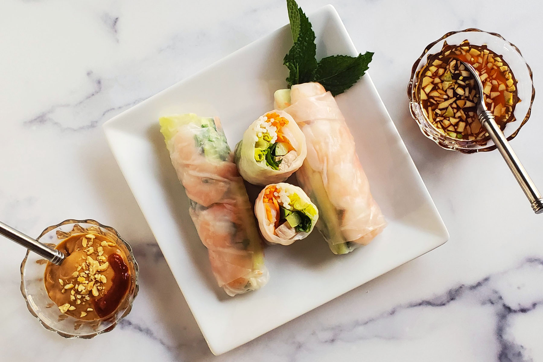 There are three Vietnamese Spring Rolls on a square, white plate. The roll in the middle is cut in half so we can see the shrimp, vegetables, pork and noodle inside. The plate is garnished with a sprig of mint leaf. On the diagonal sides, we see a peanut dipping sauce, sprinkled with crushed peanuts and sriracha on the lower left and a lighter brown colored sauce with floating pieces of mince garlic on the upper right. This is all on top of a white marble countertop.