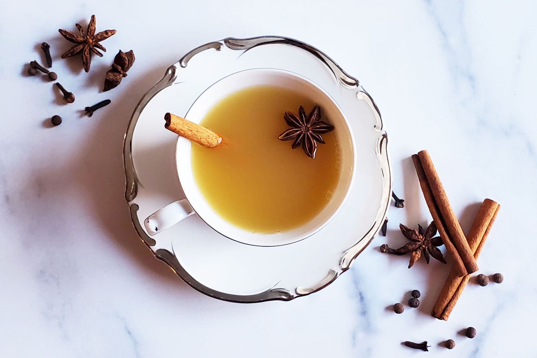 An antique teacup on a saucer, filled with wassail, a cinnamon stick and one star anise. It is in a marble counter, surrounding the cup are more spices, cinnamon sticks, clove, allspice berries and star anise.