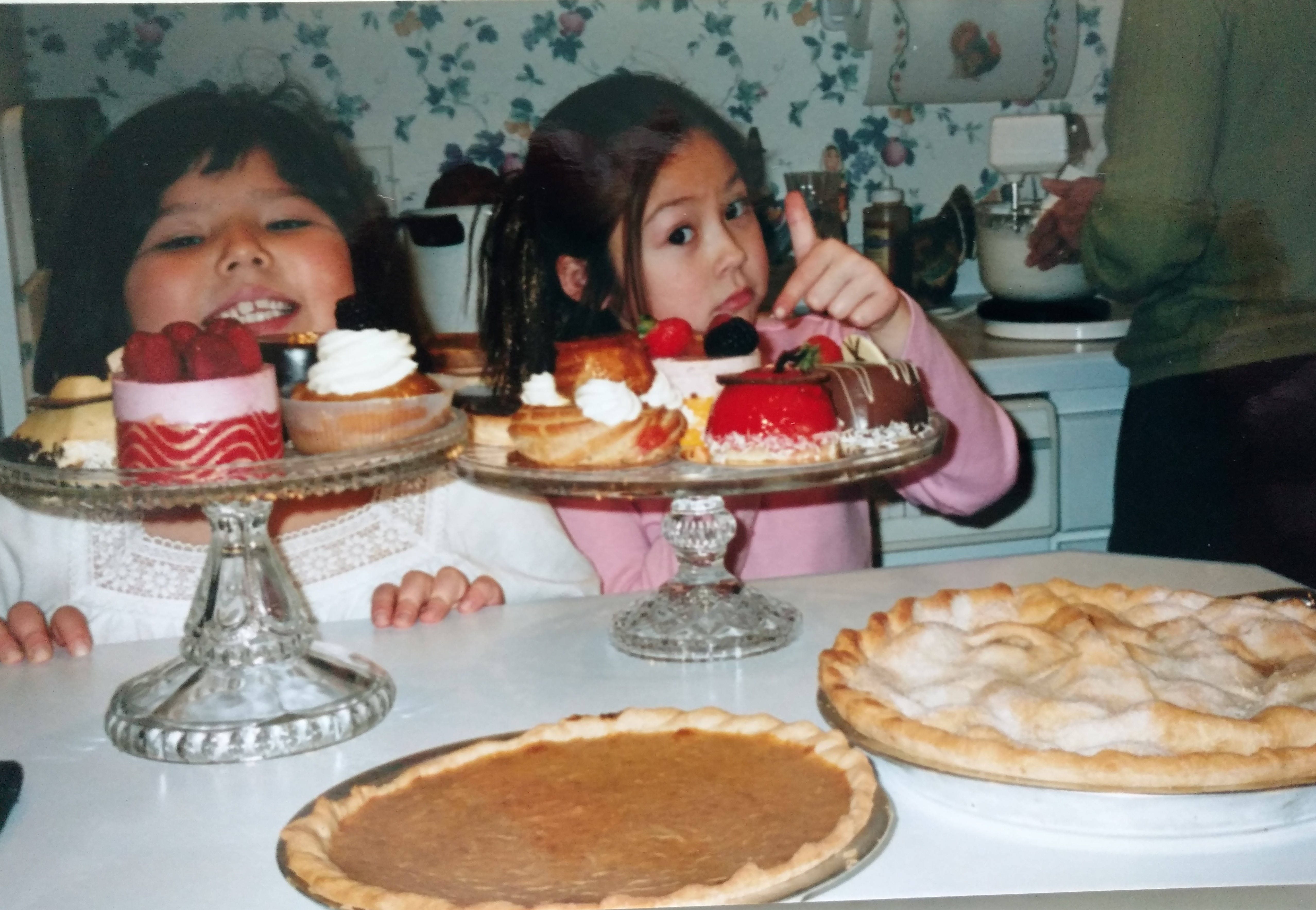 "There is floral wallpaper in the background. And the back of a woman in a green sweater, making whipped cream in a mixer. Two young half Chinese girls stand in front (my sister and I). Their heads barely peak above the cake plates that are filled with colorful pastries. Some are topped with whipped cream and berries, others with chocolate ganache. In the foreground sits freshly baked pumpkin and apple pies. The girl on the left, slightly younger smiles. While the older on the right points to the pastries with a face that looks like she's saying, ""this is the good stuff""."