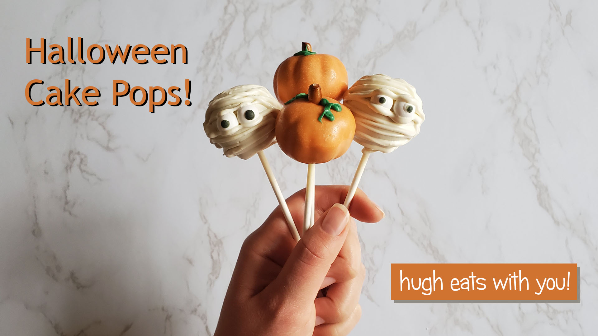 "A hand holds up mummy and pumpkin cake pops in front of a white marble background. The photo reads, ""Halloween Cake Pops!"" in the upper left corner and ""hugh eats with you"" in the bottom right corner."