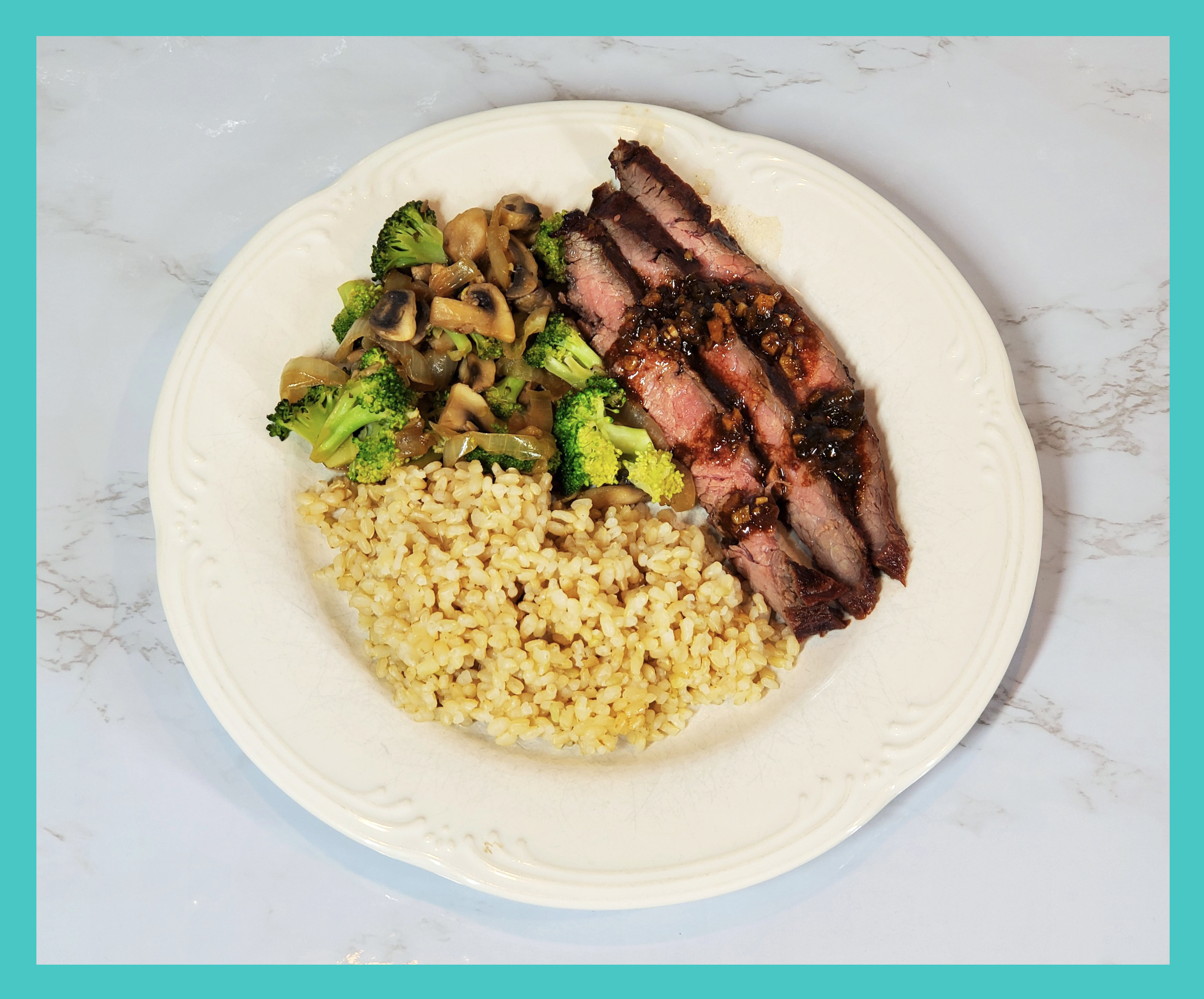 Flank Steak drizzled in sauce on a white plate with short grain brown rice, broccoli/mushrooms/onions. On a white marble background.