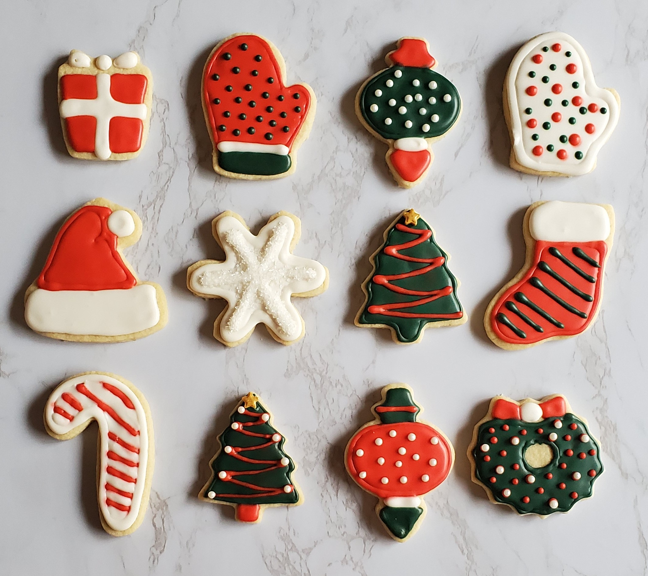 Christmas cookies in the shapes and decorated as gifts, mittens, ornaments, snowflakes, candy canes, christmas trees, wreaths and stockings. Decorated with royal icing in red white and green and sprinkles!
